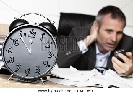 Senior businessman being shocked after receiving bad news on cell phone, sitting at office desk behind alarm clock showing five minutes to twelve.