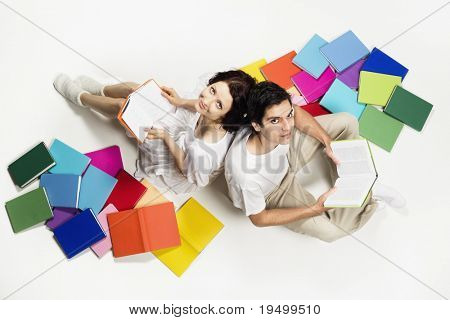 Lovely girl and boy sitting on floor with colorful books and reading, looking up, isolated on white background.