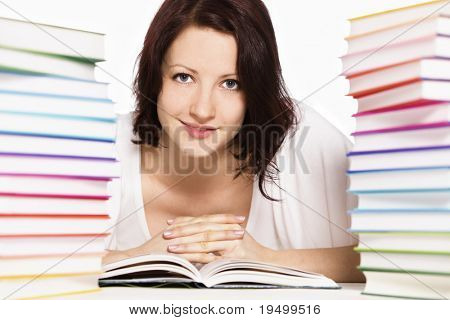 Close up of pretty smiling girl lying on floor between two stacks of colorful books reading and looking straight, isolated on white background.
