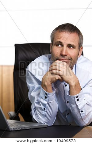 Confident senior businessman in blue shirt sitting at office desk looking upwards and contemplating,  isolated on white background.