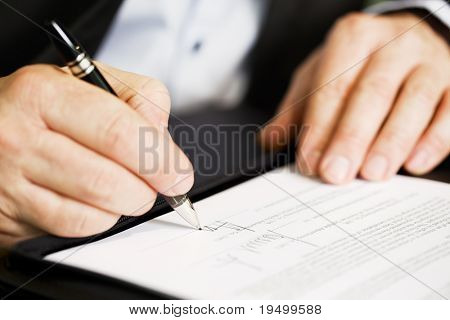 Businessman sitting at office desk signing a contract with shallow focus on signature.