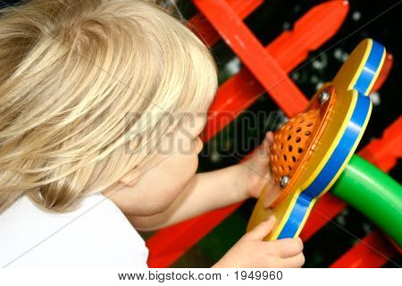 Girl Toddler Shouting Into A Flower Shaped Playground Speaker