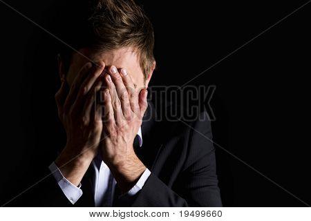 Tomar Retratos de desesperada office manager en traje oscuro que cubre su rostro con ambas manos, aislar