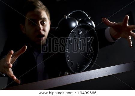 Young desperate business person in dark suit at office desk reaching alarm clock showing five minutes to twelve o'clock and trying to rescue his business, low-key image isolated on black background.
