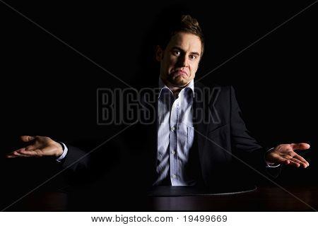 Discreto Retrato de joven empresario despistado en traje oscuro, sentado en el escritorio de oficina estar confundido, me