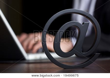 Close up of stand-alone at symbol with businessman in background in dark suit sitting at office desk working on laptop using the internet, low-key image.