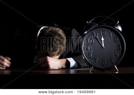 Desperate businessman in dark suit sitting at office desk with head down being in despair with close up of clock showing five minutes to twelve o-c'clock, low-key style isolated on black background.
