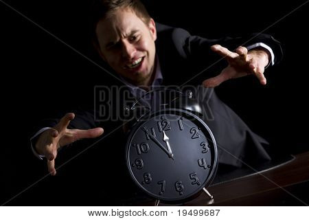 Young desperate businessman in dark suit at office desk jumping at alarm clock showing five minutes to twelve o'clock symbolizing the end is approaching, low-key image isolated on black background.