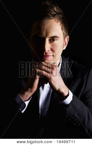 Low-key close up portrait of young smiling business executive in dark suit sitting at desk looking straight, isolated on black background
