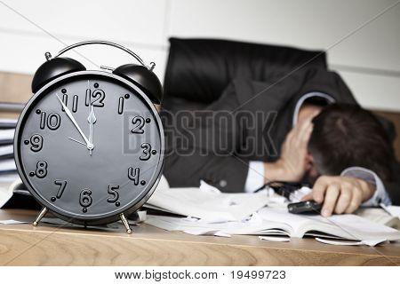 Pessoa de negócios sênior, sendo chocada depois de receber más notícias no celular, sentado na mesa do escritório