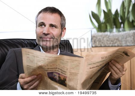 Smiling business person in dark suit sitting in office chair reading newspaper and looking up.
