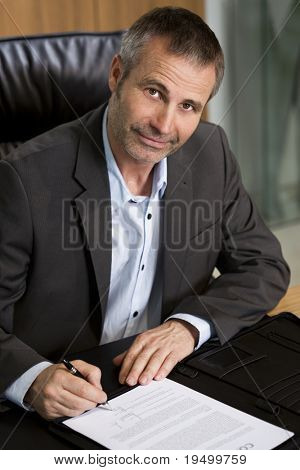 Smiling businessman in dark suit and blue shirt sitting at office desk and signing a contract, looking up.