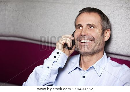 Laughing senior businessman in blue shirt sitting on sofa and talking on mobile phone.