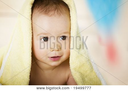 Close up of happy smiling caucasian baby boy covered with yellow blanket lying on floor.