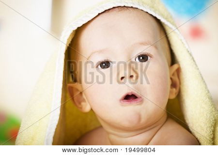 Close up portrait of sweet naked baby boy with yellow towel on head looking innocently with colorful background.
