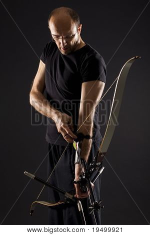 Handsome bowman in black drawing a bow, isolated on black background.