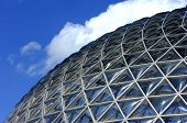 foto of geodesic  - Geodesic dome construction with blue sky and clouds - JPG