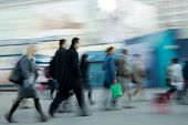 Group of people rushing to work at the morning in intentional motion blur.