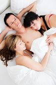 picture of threesome  - Successful man lying with two girls in bed - JPG