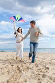 stock photo of woman dragon  - Happy outdoor couple embracing and running on beach  a kite fly - JPG