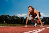 foto of athletic woman  - Athletic woman on track starting to run - JPG