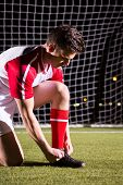 Young male soccer player tying shoelace against goal post on soccer field poster
