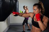 Determined women practicing boxing in fitness studio poster