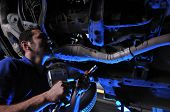 image of auto repair shop  - Auto mechanic working under dramatically lightened car  - JPG