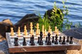 Постер, плакат: Chess Board With Chess Pieces On Rock With River Embankment Background