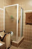 stock photo of shower-cubicle  - A modern shower cubicle with brown and beige tiled walls and wet floor mat 