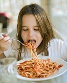 stock photo of young girls  - young girl eating spaghetti in restaurant - JPG