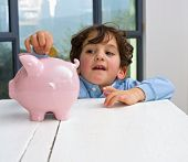 young boy holding a piggy bank