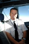 stock photo of cessna  - A handsome airline pilot enjoys hours of boredom - JPG