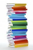 Stack of colorful real books on white background, side view.
