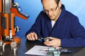 picture of calipers  - Young male engineer in blue overall measuring a metal part with caliper - JPG