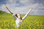 stock photo of praise  - Young woman standing in yellow rapeseed field raising her arms expressing gratitude or freedom - JPG