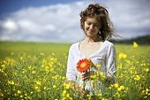 Happy woman in white dress holding red flowers in yellow rapeseed field.
