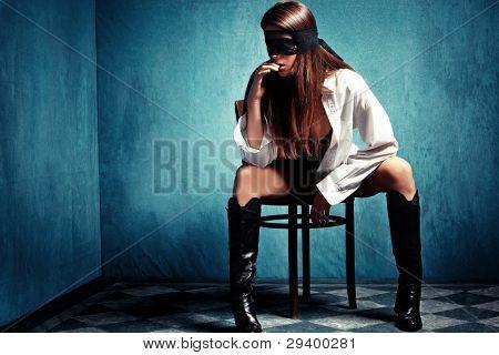 jovem sensual com laço cobrindo os olhos sentar na cadeira em botas de couro e camisa
