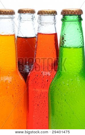Closeup of four assorted soda bottles with condensation. Vertical format over a white background.