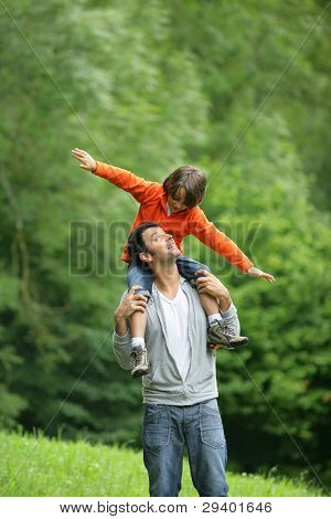 Little boy sat on father's shoulders