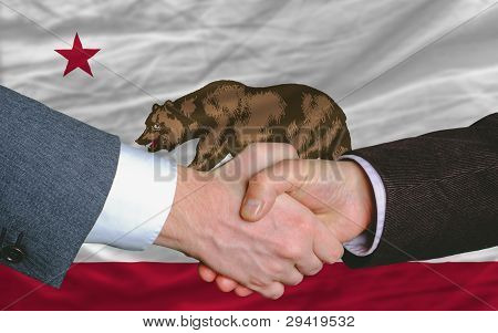 In Front Of American State Flag Of California Two Businessmen Handshake After Good Deal