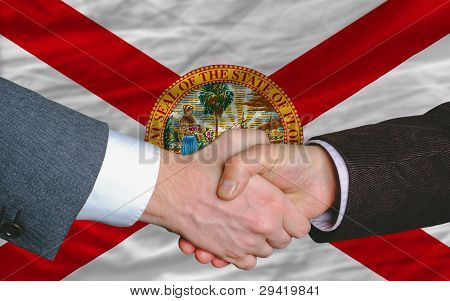 In Front Of American State Flag Of Florida Two Businessmen Handshake After Good Deal