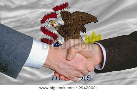 In Front Of American State Flag Of Illinois Two Businessmen Handshake After Good Deal