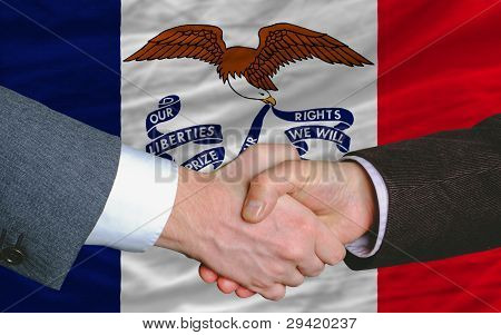 In Front Of American State Flag Of Iowa Two Businessmen Handshake After Good Deal