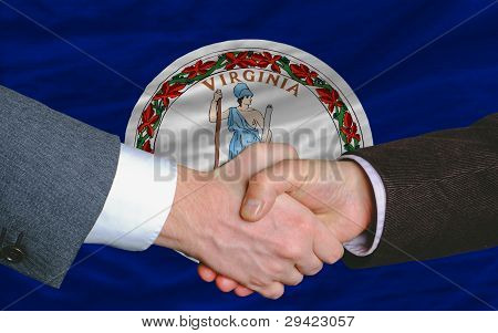 In Front Of American State Flag Of Virginia Two Businessmen Handshake After Good Deal