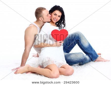 Happy young adult couple with red heart on the floor embracing and laughing