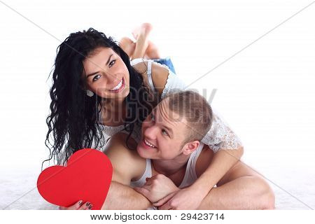 Happy young adult couple with red heart lie on the floor embracing and laughing