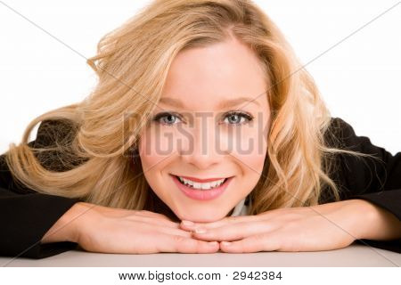Blond Smiling Woman Laying On Her Desk