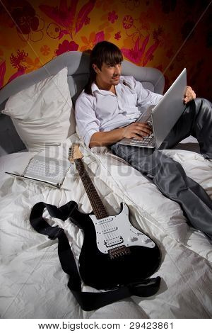 Young man  with guitar and a laptop on bed