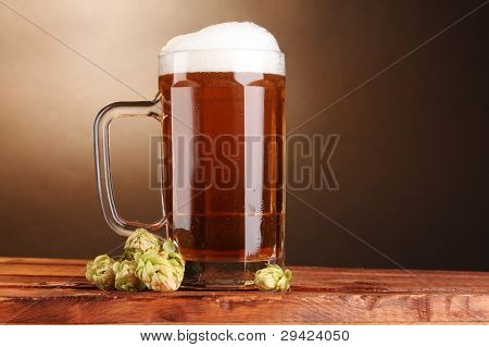 beer mug and green hop on wooden table on brown background